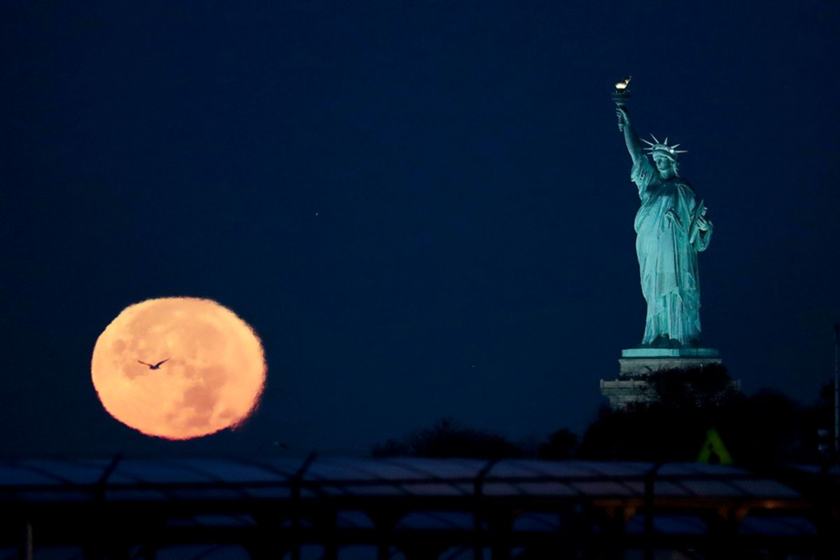 The supermoon appears near the Statue of Liberty, Monday, Nov. 14, 2016, in New York. Monday's supermoon, a phenomenon that happens when the moon makes a close pass at the earth, is the closest to earth since 1948. (AP Photo/Julio Cortez) (AP)