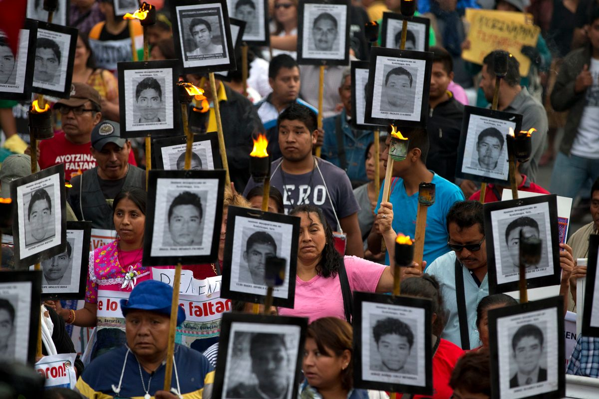 FILE - In this April 26, 2016 file photo, family members and supporters of 43 missing teachers college students carry pictures of the students as they march to demand the case not be closed and that experts' recommendations about new leads be followed, in Mexico City. In Mexico's ten year war on drugs advances can be seen in places like the violent border city of Ciudad Juarez, where the number of homicides fell when it began a stepped-up policing effort. But those kind of gains haven't been seen in most other states. (AP Photo/Rebecca Blackwell, File) (AP)