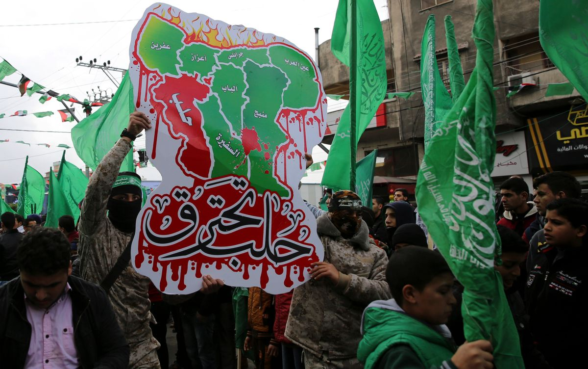 """Masked Palestinian militants from the Izzedine al-Qassam Brigades, a military wing of Hamas, hold a poster of a Syrian map with Arabic text that reads, """"Aleppo is burning,"""" as others wave green Islamic flags during a rally to commemorate the 29th anniversary of its founding, in Gaza City, Wednesday, Dec. 14, 2016. Hamas overtook Gaza by force in 2007 after routing troops loyal to Palestinian President Mahmoud Abbas in bloody street battles. Palestinians have been divided since between Gaza under Hamas and Abbas governing parts of the West Bank. () (AP Photo/Adel Hana)"""