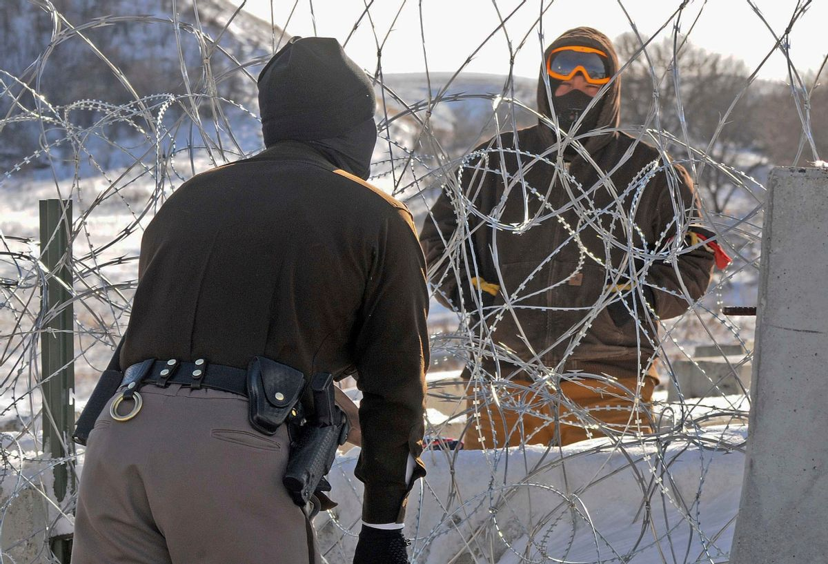 A law enforcement officer speaks to a protester against the Dakota Access Pipeline through a wall of razor wire on the Backwater Bridge over Cantapeta Creek on Thursday afternoon, Dec. 8, 2016. Protesters have been trespassing at the site and cutting wire in attempts to gain access to the pipeline work area in southern Morton County. (Tom Stromme/The Bismarck Tribune via AP) (AP)