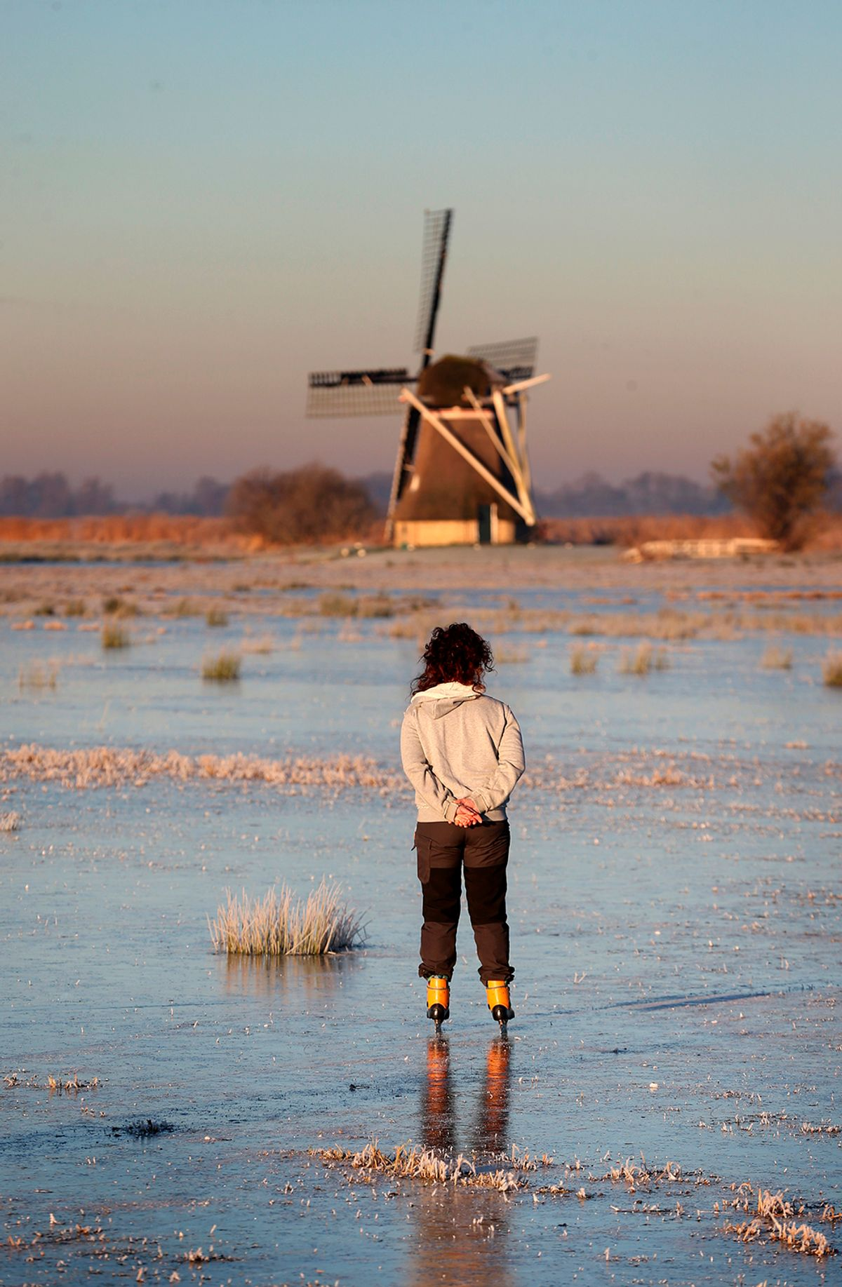 An ice skaters on nature skate near a mill in the Ryptsjerksterpolder in Tietjerk, on December 5, 2016.  / AFP / ANP / Catrinus van der Veen / Netherlands OUT        (Photo credit should read CATRINUS VAN DER VEEN/AFP/Getty Images) (Afp/getty Images)
