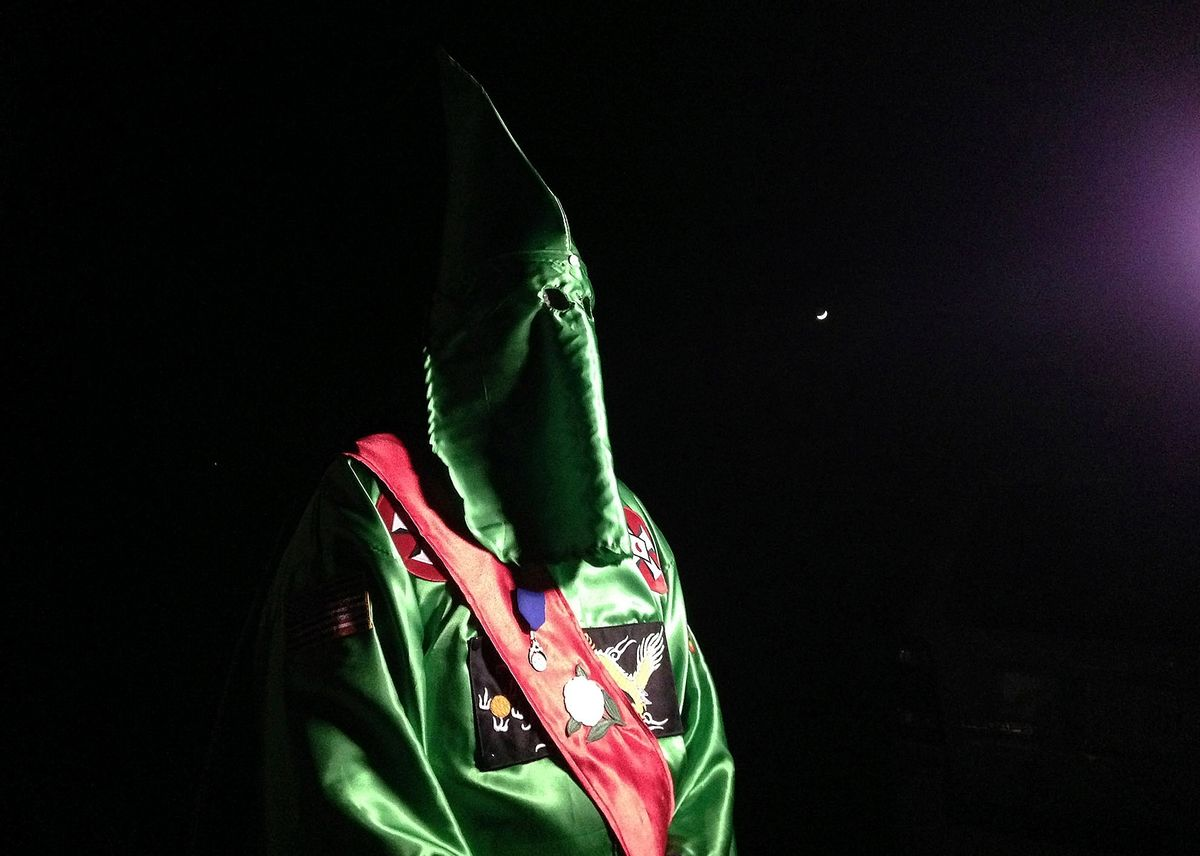 """In this photo taken Friday, Dec. 2, 2016, a robed and masked Ku Klux Klansmen stands on a muddy dirt road during an interview near Pelham, N.C. The KKK and other white extremist groups don't like being called """"white supremacists,"""" a phrase that dates to the earliest days of white racist movements in the United States. () (AP Photo/Jay Reeves)"""