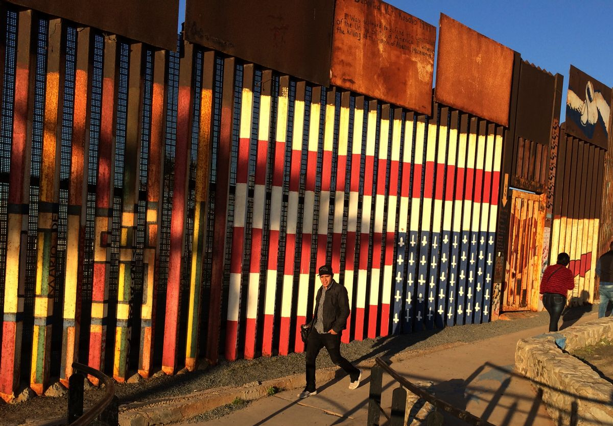"""People pass graffiti along the border structure in Tijuana, Mexico, Wednesday, Jan. 25, 2017. President Donald Trump moved aggressively to tighten the nation's immigration controls Wednesday, signing executive actions to jumpstart construction of his promised U.S.-Mexico border wall and cut federal grants for immigrant-protecting """"sanctuary cities."""" () (AP Photo/Julie Watson)"""