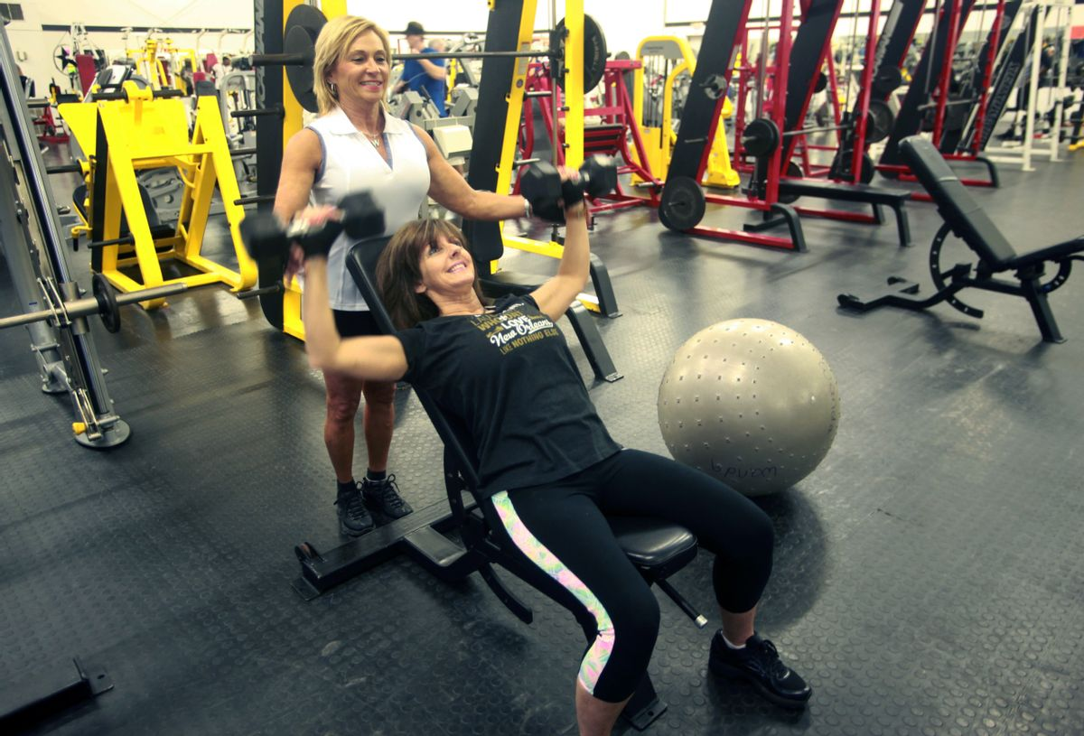 In this June 13, 2016 photograph, Wanda Downs, left, assists Christie Purvis of Tallulah, La., with an incline bench press using dumbbells during their training session at Wyatt's Gym in Vicksburg, Miss. Health clubs and gyms have dropped their rates and initiation fees sharply in the years since the recession, according to the International Health, Racquet & Sportsclub Association. This is partly due to competition from high-volume, low-price chains like Planet Fitness and others that charge under $20 a month. (John Surratt/The Vicksburg Post via AP) (AP)