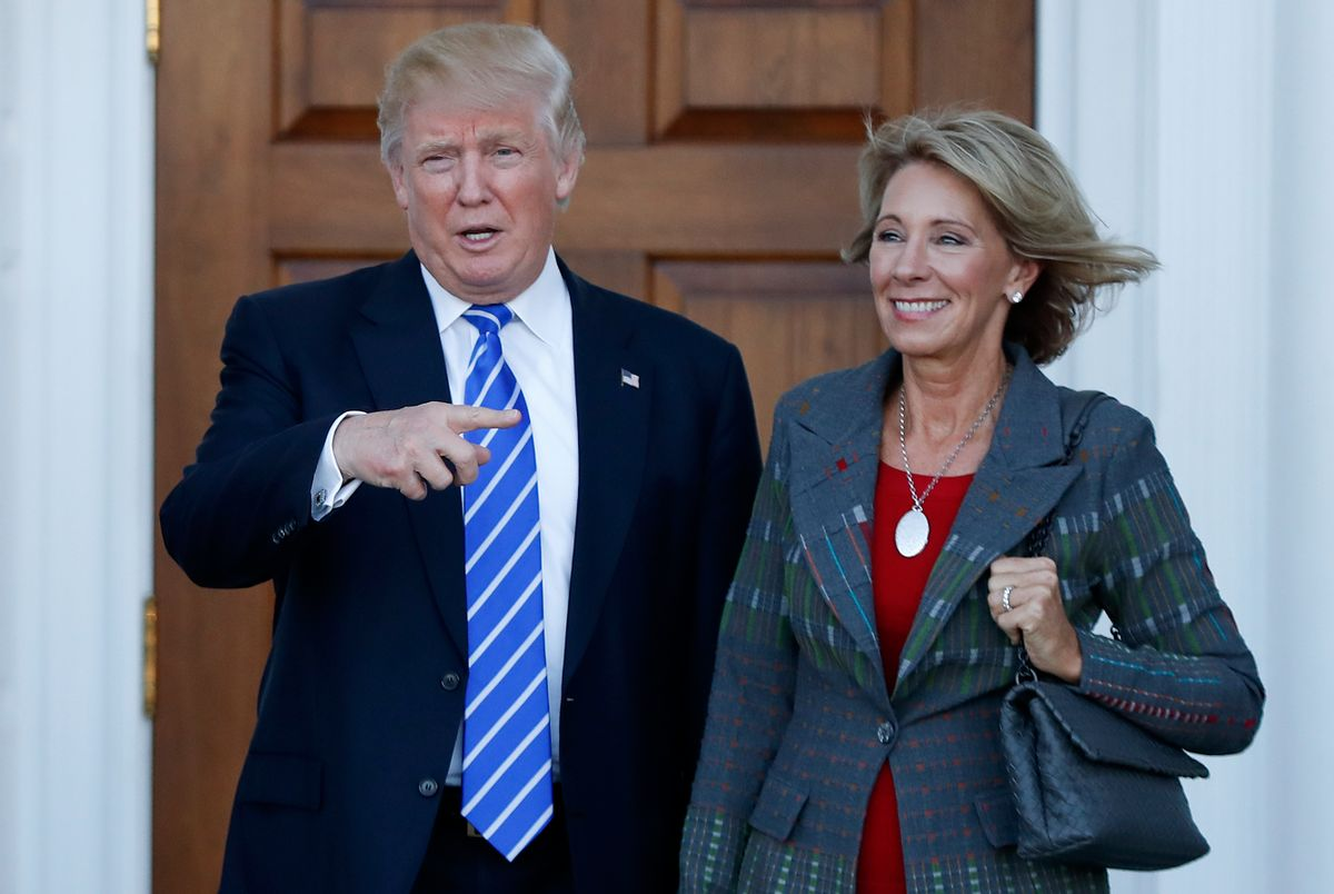 FILE - In this Nov. 19, 2016 file photo, President-elect Donald Trump stands with Education Secretary-designate Betsy DeVos in Bedminster, N.J.  DeVos has spent over two decades advocating for school choice programs, which give students and parents an alternative to traditional public school education. Her confirmation hearing was scheduled for Jan. 17. (AP Photo/Carolyn Kaster, File) (AP Photo/Carolyn Kaster)