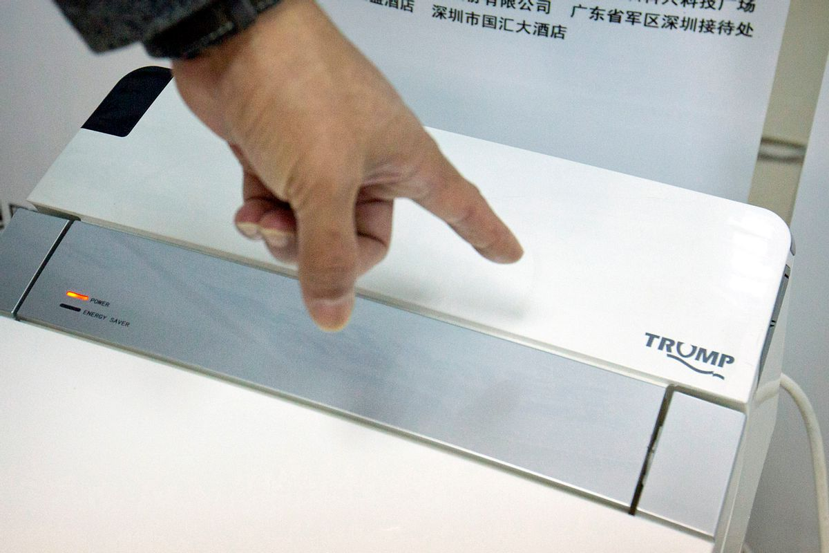 In this Monday, Feb. 13, 2017 photo, Zhong Jiye, a co-founder of Shenzhen Trump Industrial Co., points to the logo on one of his firm's high-end Trump-branded toilets at the company's offices in Shenzhen in southern China's Guangdong Province. U.S. President Donald Trump is poised to receive something that he had been trying to get from China for more than a decade: trademark rights to his own name. After suffering rejection after rejection in China's courts, he saw his prospects change dramatically after starting his presidential campaign. (AP Photo/Mark Schiefelbein) (AP)