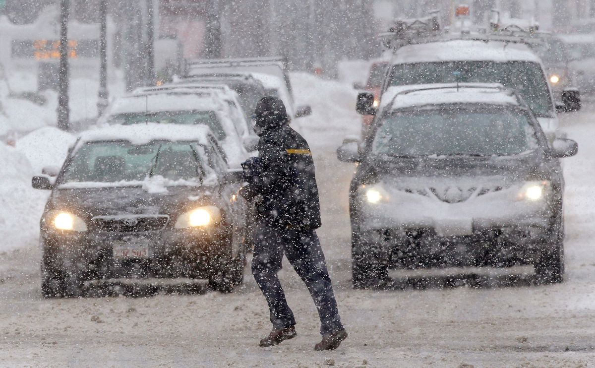 A pedestrian crosses the street in front of vehicles during a snowstorm, Sunday, Feb. 12, 2017, in Waltham, Mass. (AP Photo/Steven Senne) (AP)