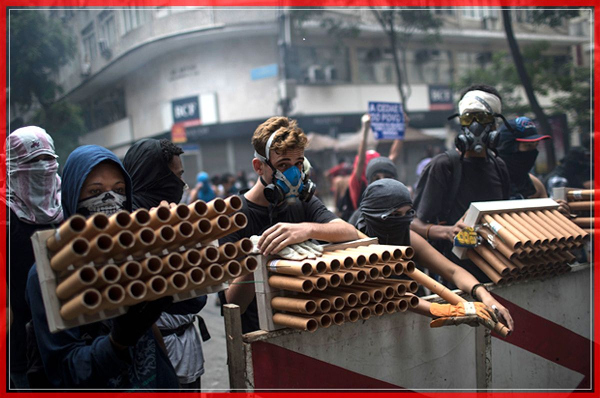 Demonstrators holding fireworks as weapons stand behind a barricade during clashes with police as they protest the state government in Rio de Janeiro, Brazil, Thursday, Feb. 9, 2017.  The protesters are denouncing a proposal to privatize the state's water and sewage company. (AP Photo/Felipe Dana) (AP)