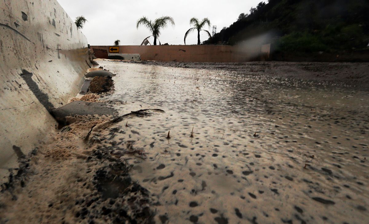 Raindrops splash in water, mud and debris in a basin slowly filling up in Duarte, Calif., in a threatened area below a burn area know as the Fish Fire, as a powerful storm moves into Southern California Friday, Feb. 17, 2017. The saturated state faces a new round of wet weather that could trigger flooding and debris flows. (AP Photo/Reed Saxon) (AP Photo/Reed Saxon)