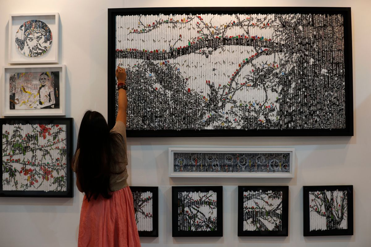 Vinila Dasgupta retouches her art during India Art Fair in New Delhi, India, Thursday, Feb. 2, 2017. The four day art fair brings together a number of modern and contemporary artists to present their works. ( (AP Photo/Tsering Topgyal))