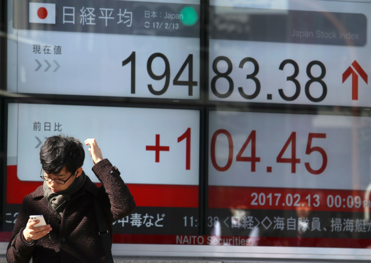 A man uses a mobile phone in front of an electronic stock indicator of a securities firm in Tokyo, Monday, Feb. 13, 2017.   (AP Photo/Shizuo Kambayashi) (AP)