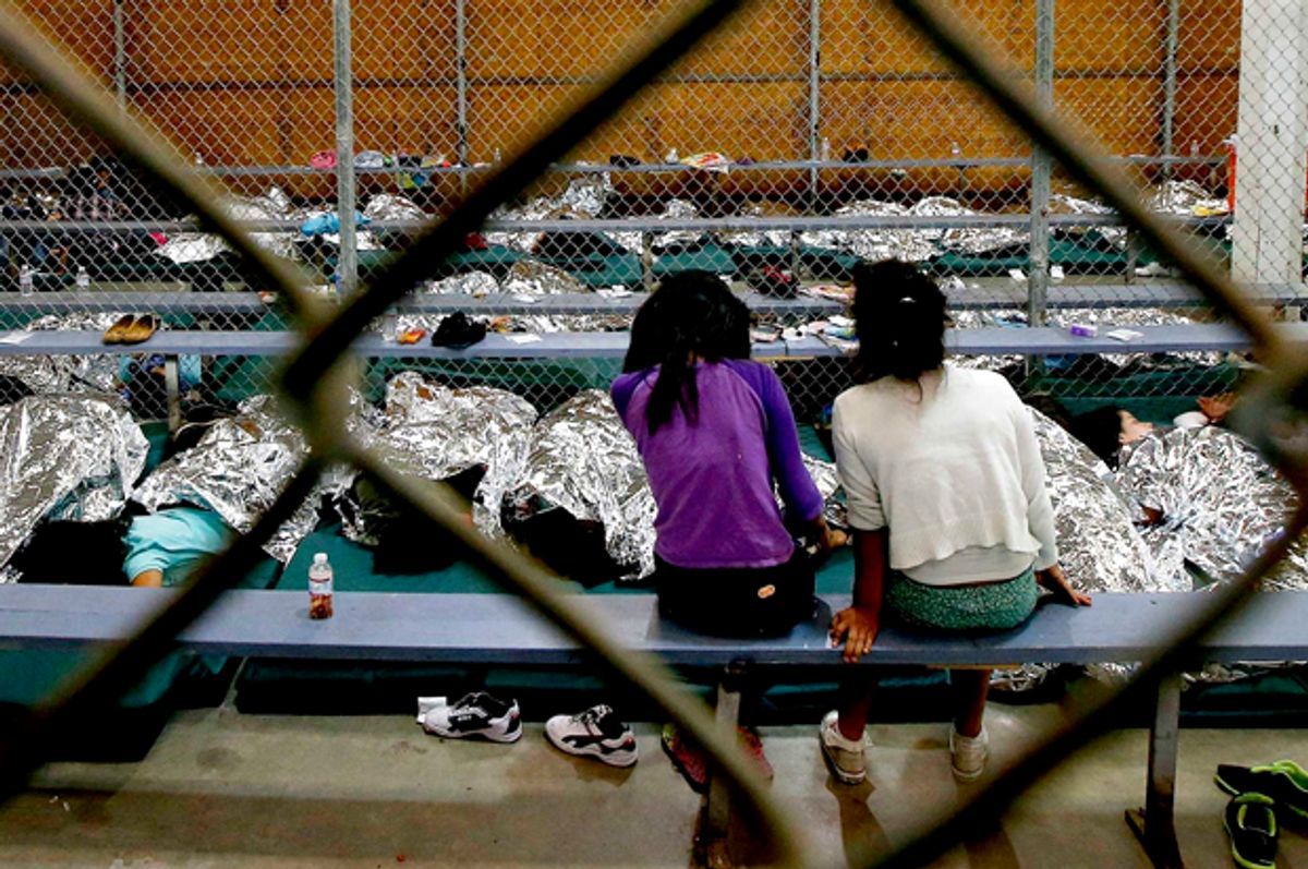 Two young girls watch television from their holding area where hundreds of mostly Central American immigrant children are being processed and held at the U.S. Customs and Border Protection Nogales Placement Center   (AP/Ross D. Franklin)