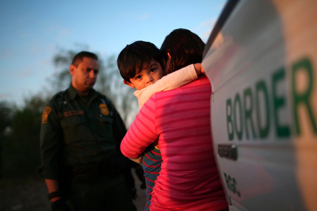 A one-year-old from El Salvador clings to his mother after she turned themselves in to Border Patrol agents on December 7, 2015 near Rio Grande City, Texas   (Getty/John Moore)