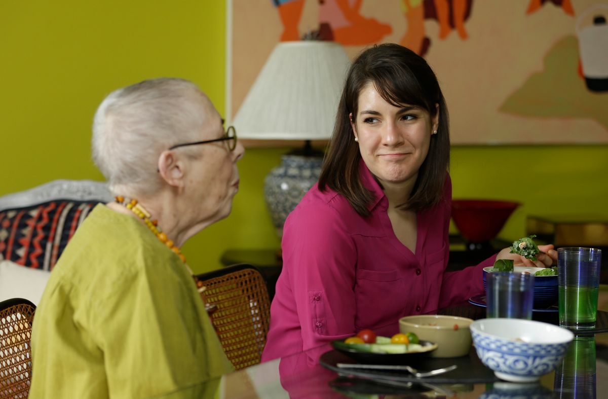 In this Friday, Feb. 17, 2017 photo, Laura Berick, left, a retired art dealer, has lunch with Justine Myers at Berick's home at Judson Manor, in Cleveland. In a research project, graduate-level students live among residents of the Judson Manor retirement home. The study looks at the impact of isolation and loneliness, aging and stereotypes of retirees by students and vice versa. Myers is an artist-in-residence at Judson Park. She is an Oberlin College graduate student studying music. (AP Photo/Tony Dejak) (AP)