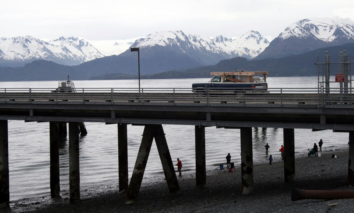 In this May 24, 2015, photo a vehicle drives on a pier to be loaded onto an Alaska state ferry while people fish underneath the pier in Homer, Alaska.  (AP Photo/Mark Thiessen)