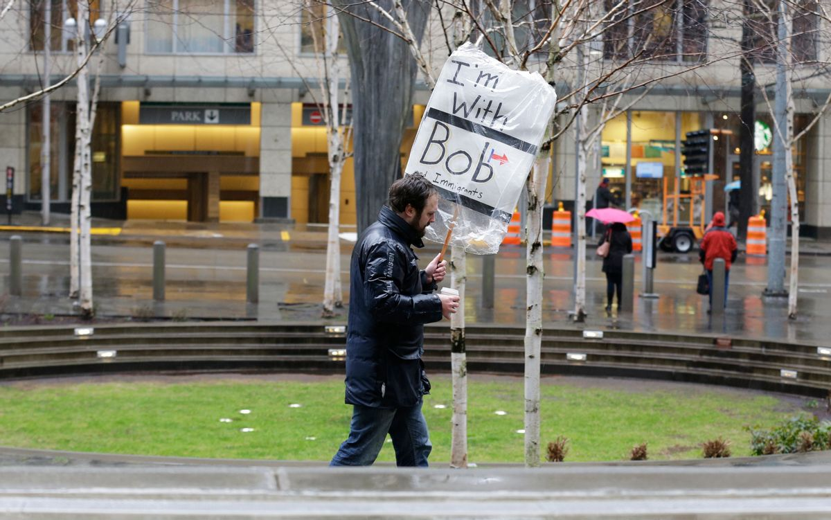 """A person walks outside the federal courthouse in Seattle carrying a sign that reads """"I'm with Bob and Immigrants,"""" in reference to Washington state Attorney General Bob Ferguson, Friday, Feb. 3, 2017, during a hearing in federal court. A U.S. judge on Friday temporarily blocked President Donald Trump's ban on people from seven predominantly Muslim countries from entering the United States after Washington state and Minnesota urged a nationwide hold on the executive order that has launched legal battles across the country. (AP Photo/Ted S. Warren) (AP)"""