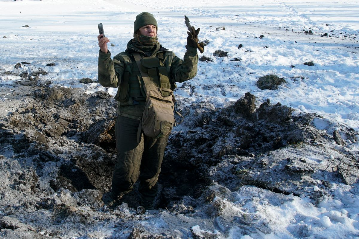 A Ukrainian soldier shows pieces of shrapnel in a crater left by an explosion in Avdiivka, Ukraine, Tuesday, Jan. 31, 2017. Fighting between government troops and Russia-backed separatist rebels in eastern Ukraine escalated on Tuesday, killing at least eight people late Monday and early Tuesday, injuring dozens and briefly trapping more than 200 coal miners underground, the warring sides reported.() (AP Photo/Inna Varenytsia)