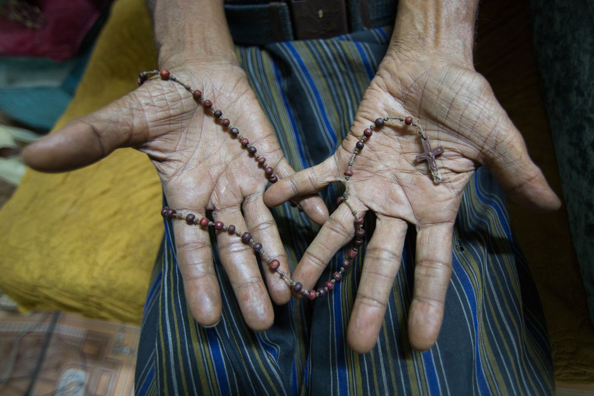 A member of the last remaining originally Christian family in Aden holds a rosary in his hands. Their priest was Father Tom, who was kidnapped last year and is still being held by ISIS. (Maria De La Guardia/Narratively)