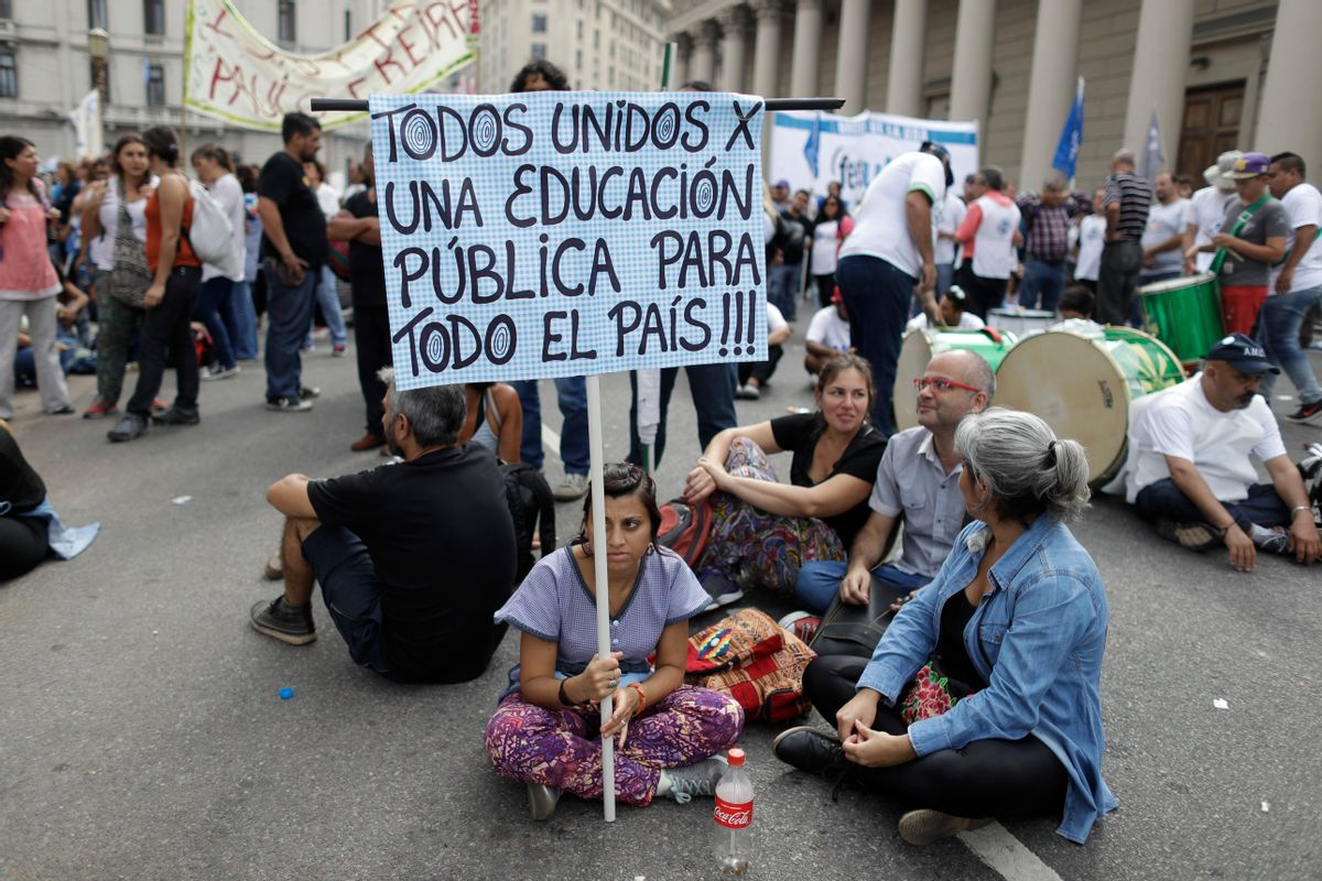 """A teacher holds a sign with a message that reads in Spanish: """"All united for public education for the entire country"""", during a protest demanding higher wages in Buenos Aires, Argentina, Wednesday, March 22, 2017. Tens of thousands of teachers marched to Plaza de Mayo, the park overlooking the presidential palace, during their fourth day of national strike. (AP Photo/Victor R. Caivano) (AP)"""