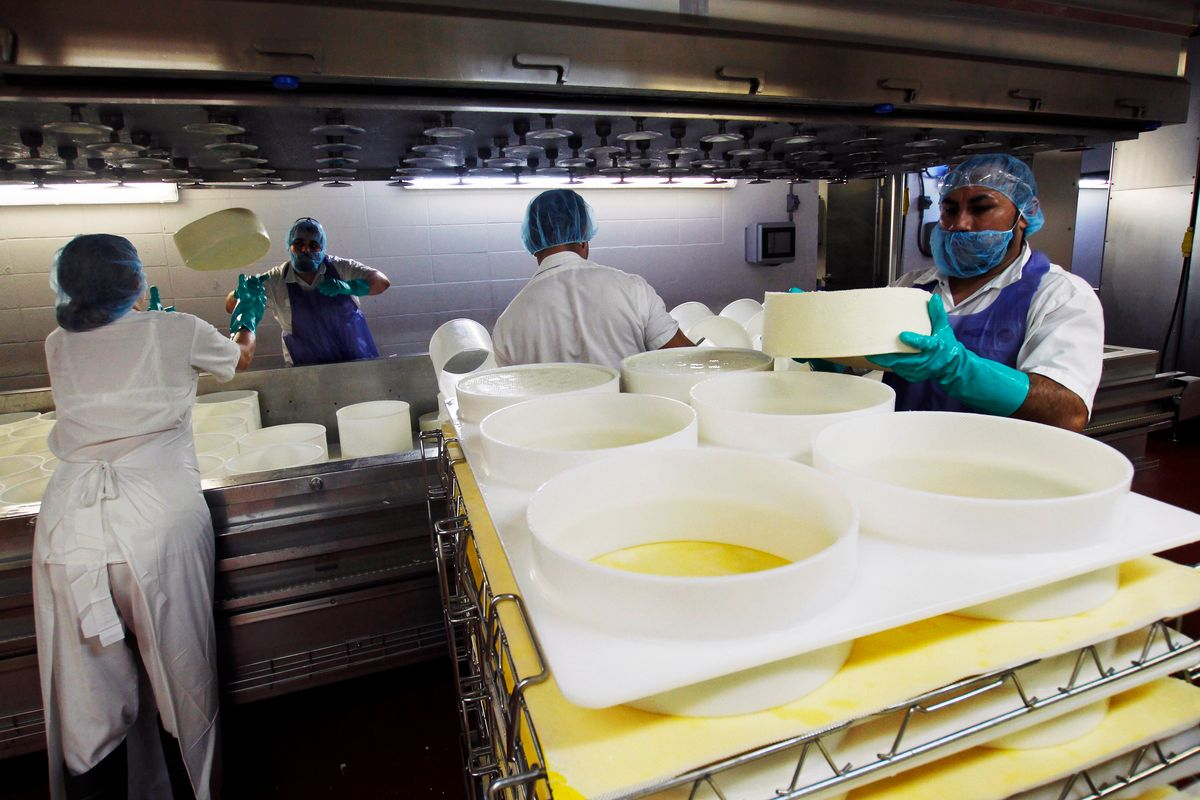 In this Feb. 27, 2017, photo, Brenda Patterson, left, is about to catch a wheel of Grand Cru Surchoix cheese at the Emmi Roth USA production plant in Monroe, Wis. The company won the World Championship Cheese Contest in 2016 for the cheese and since then has seen an increase in sales of the cheese. The contest is organized by the Wisconsin Cheese Makers Association, which also organizes the United States Championship Cheese Contest that runs until March 9 in Green Bay, Wis. The contests are in alternate years. (AP Photo/Carrie Antlfinger) (AP)