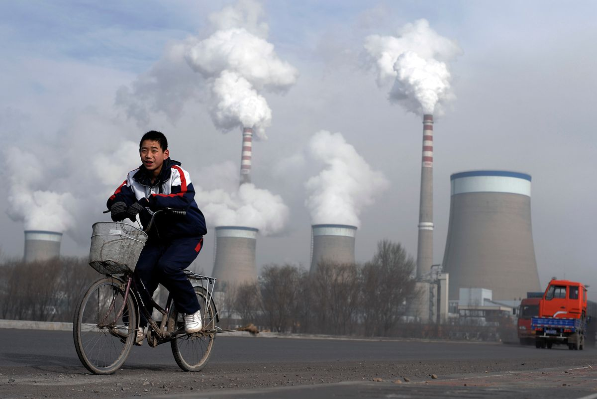 FILE - In this Dec. 3, 2009 file photo, a Chinese boy cycles past cooling towers of a coal-fired power plant in Dadong, Shanxi province, China. Led by cutbacks in China and India, construction of new coal-fired power plants is falling worldwide, improving chances climate goals can be met despite earlier pessimism, three environmental groups said Wednesday, March 22, 2017. (AP Photo/Andy Wong, File) (AP)