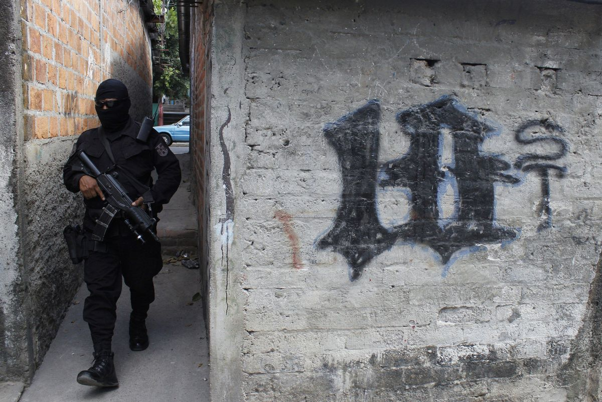 FILE - This April 5, 2016 file photo shows a masked, armed police officer patrolling a gang controlled neighborhood in San Salvador, El Salvador. Government statistics show a sharp drop in homicides so far in 2017 after the gang-plagued country posted some of the world's highest murder rates in recent years, according to National police Commissioner Howard Cotto on March 1, 2017.  (AP Photo/Alex Peña, File) (AP)