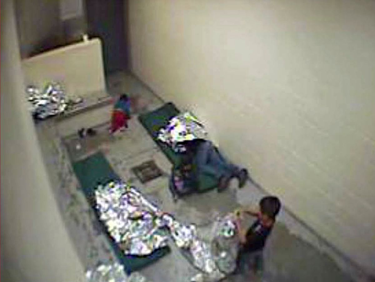 FILE- This September, 2015 file image made from U.S. Border Patrol surveillance video shows a child crawling on the concrete floor near the bathroom area of a holding cell, and a woman and children wrapped in Mylar sheets at a U.S. Customs and Border Protection station in Douglas, Ariz. A federal judge says the Border Patrol in Arizona violated court orders by failing to properly keep surveillance video pertaining to a lawsuit claiming the agency holds migrants in inhumane conditions. Judge David Bury partially granted a motion on Monday, March 13, to hold the Border Patrol's Tucson Sector in civil contempt over video files it was legally required to provide but which were irreparably damaged.(U.S. Border Patrol via AP, File) (AP)
