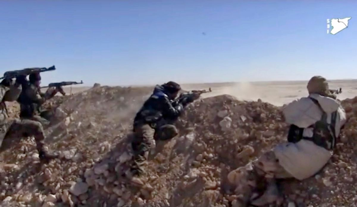FILE - This frame grab from a  March 6, 2017 video provided by the Syria Democratic Forces (SDF), shows fighters from the SDF opening fire on a position of the Islamic State group in the countryside east of Raqqa, Syria. As the American –backed SDF fighters bear down on Raqqa, the militants have trapped the city's estimated 300,000 residents to use as human shields, ringing the city with land mines to prevent escape. (Syria Democratic Forces, via AP, File) (AP)