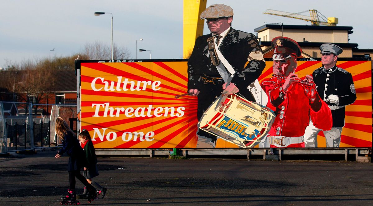 Children walks past a Loyalist mural in East Belfast a predominantly loyalist area in Belfast, Northern Ireland, Friday, March 24, 2017. Almost 20 years on from the Good Friday peace accord, which brought about the end of Northern Ireland's sectarian conflict, the city of Belfast has changed dramatically. Reminders of the past are everywhere _ murals and memorials to those killed in the conflict, along with peace walls that separate predominantly Protestant neighborhoods from mostly Catholic ones _ but there are also new shopping malls and cafes, new tech industries, and lots of tourists. (AP Photo/Peter Morrison) (AP)