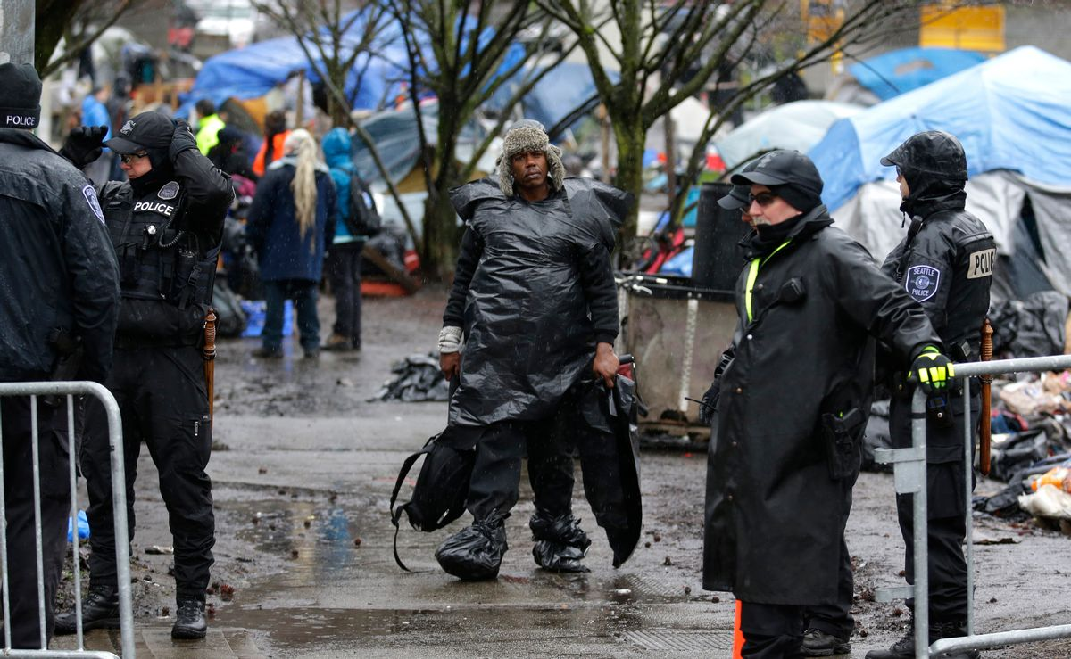 """In this March 7, 2017 photo, a man wearing plastic bags in the rain carries belongings as he walks during a sweep to clear out people living at a homeless encampment known as """"The Field,"""" in Seattle's Stadium district south of downtown. Sixteen months after he declared a state of emergency on homelessness, Seattle's mayor is asking voters in this liberal, affluent city for $55 million a year in new taxes to fight the problem. (AP Photo/Ted S. Warren) (AP)"""