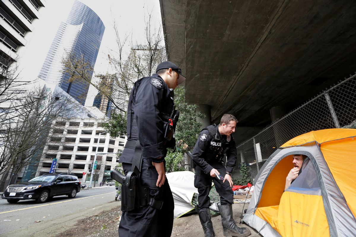 In this photo taken Thursday, March 23, 2017, Seattle police officers Wes Phillips, left, and Tori Newborn talk with Corvin Dobschutz as part of a new team of outreach workers and officers that go out and connect homeless people to services, as the homeless man sits in his tent below a freeway and next to downtown Seattle. (AP Photo/Elaine Thompson) (AP)