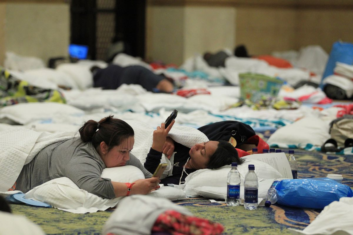 Guests try to pass the time in the ballrooms of the Atlantis Paradise Island Hotel, as Hurricane Matthew moves away from the resort island in Nassau, Bahamas, Thursday, Oct. 6, 2016. (AP Photo/Tim Aylen)