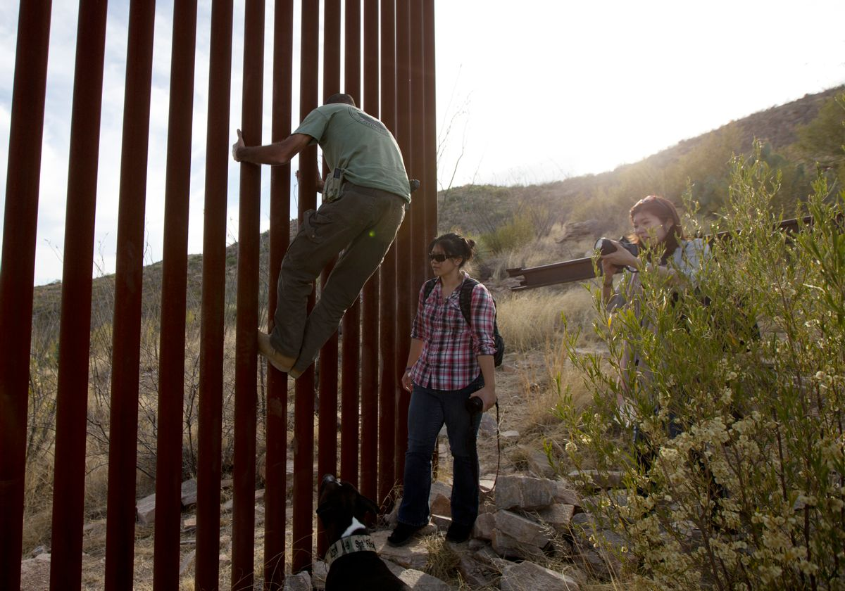 FILE - In this May 11, 2016, file photo, Tim Foley shows how to climb a section of the border wall separating Mexico and the United States near where it ends as journalists Chitose Nakagawa, right, and Marcie Mieko Kagawa look on in Sasabe, Ariz. Foley, a former construction foreman, founded Arizona Border Recon, a group of armed volunteers who dedicate themselves to border surveillance. With bids due Tuesday, April 4, 2017, on the first border wall design contracts, companies are preparing for the worst if they get the potentially lucrative but controversial job. (AP Photo/Gregory Bull, File) (AP)