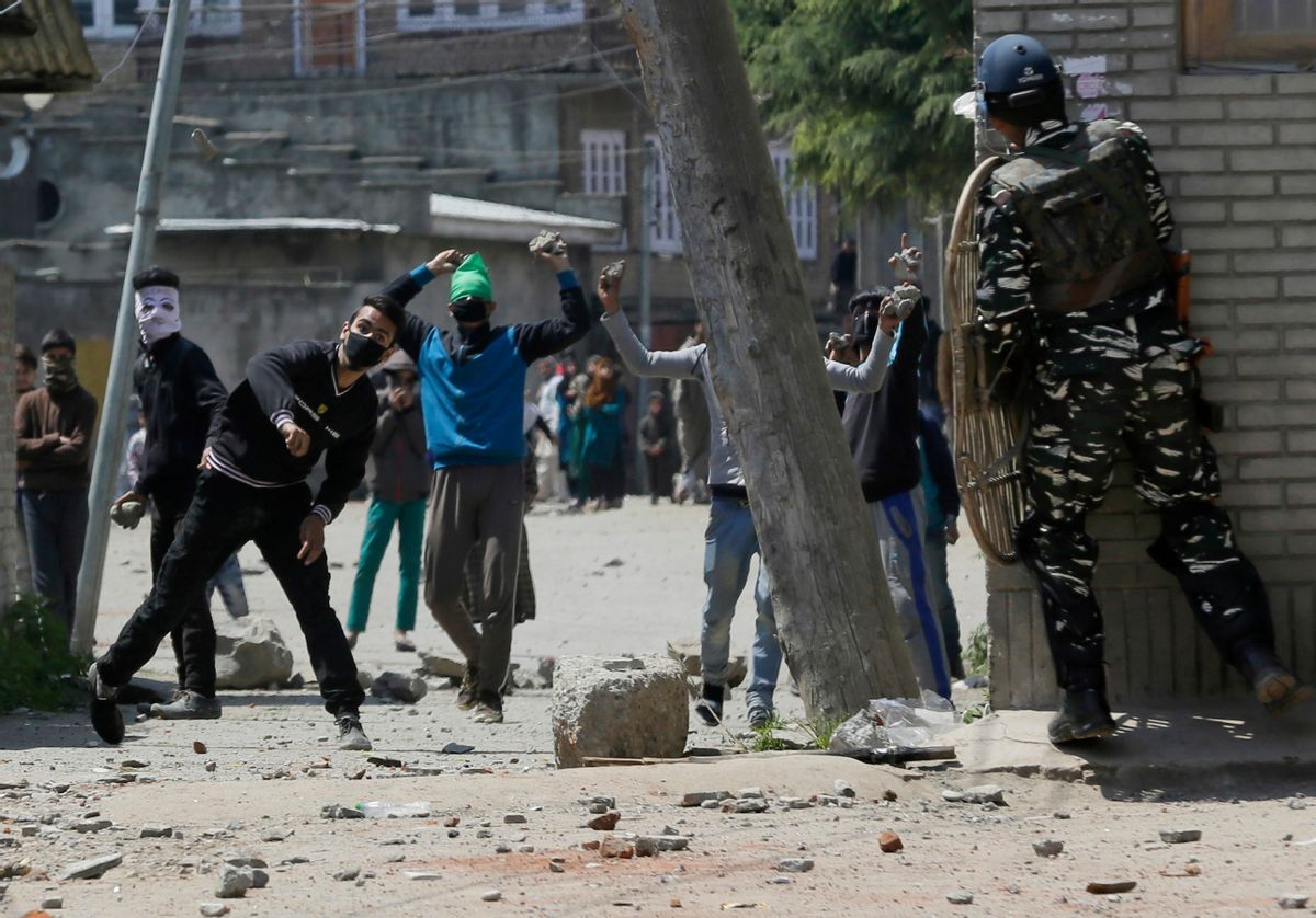 Kashmiri protesters throw stones on Indian security men outside a poling station during a by-election to an Indian Parliament seat in Srinagar, Indian controlled Kashmir, Sunday, April. 9, 2017. (AP Photo/Mukhtar Khan) (AP)