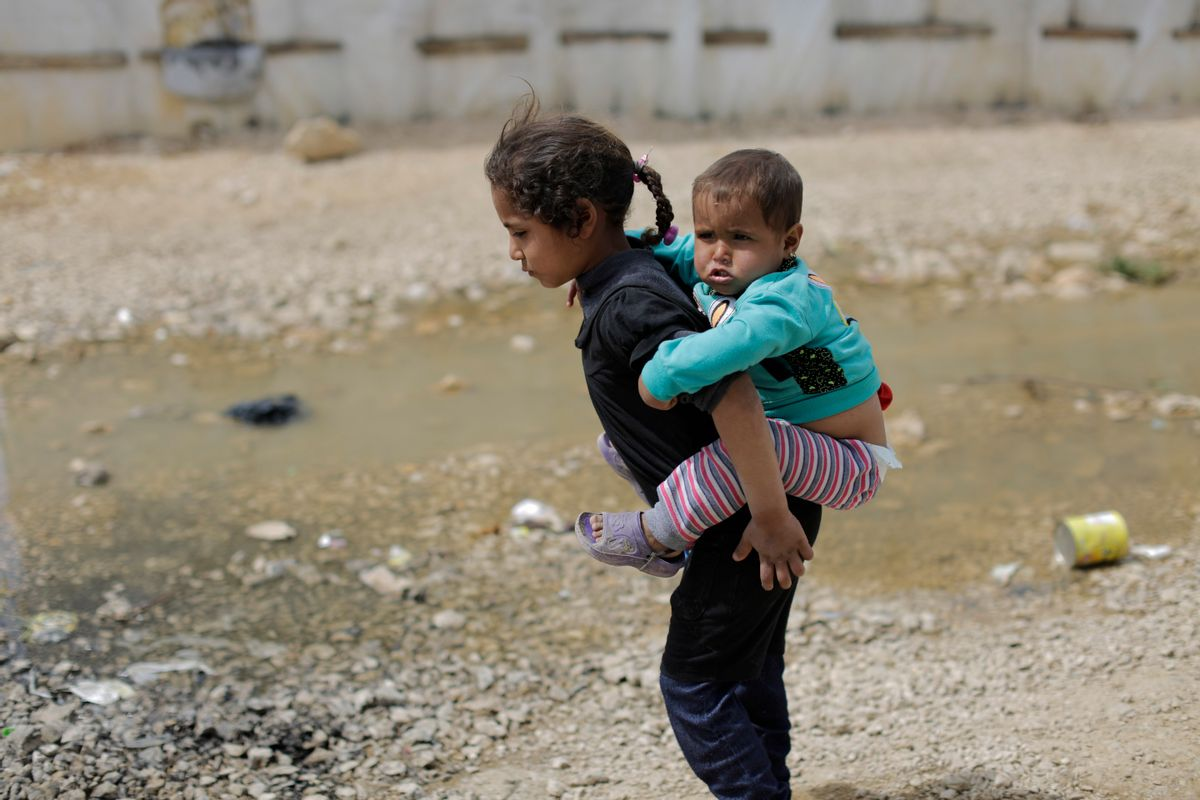 A Syrian refugee girl holds her brother as she walks at an informal refugee camp, at Al-Marj town in Bekaa valley, east Lebanon Lebanon, Saturday, April 8, 2017. For the millions of Syrian refugees scattered across camps and illegal settlements across the region, the chemical attack on a town in northern Syria and subsequent U.S. strike was a rare moment when the world briefly turned its attention to Syria, before turning away again. (AP Photo/Hassan Ammar) (AP Photo/Hassan Ammar)
