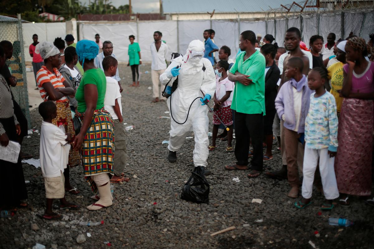FILE - In this file photo daetd Tuesday, Sept. 30, 2014, a medical worker sprays people being discharged from the Island Clinic Ebola treatment center in Monrovia, Liberia. Bulldozers on Wednesday April. 5, 2017 cleared the remains of a once busy Ebola treatment unit in Liberia, as health care workers, officials and some who were treated there gathered to mark the center's last day and official decommissioning. (AP Photo/Jerome Delay, FILE) (AP)
