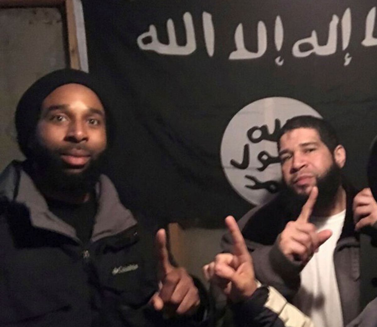 In this undated photo provided by the Federal Bureau of Investigation Joseph D. Jones, left, and Edward Schimenti pose in front of an Islamic State group flag. Jones and Schimenti were arrested by FBI agents on Wednesday, April 12, 2017 on terrorist charges for allegedly conspiring to support the Islamic State militant group. (FBI via AP) (AP)