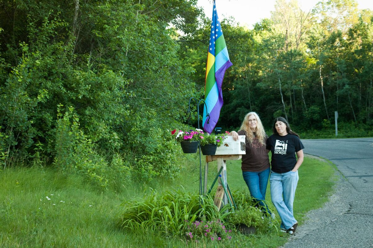 The author, left, and Wendy, with their flag at the end of their drive. (Chris LeRoux/Narratively)