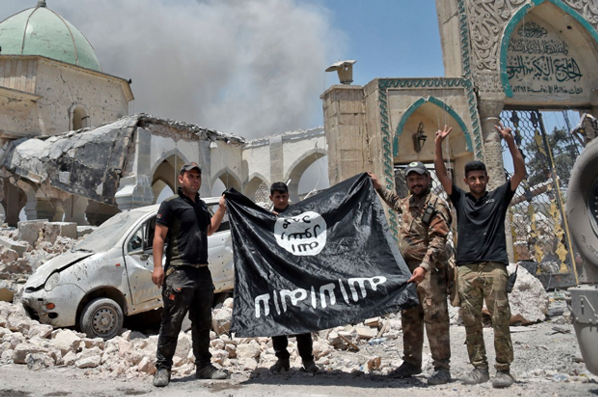 Members of the Iraqi Counter-Terrorism Service (CTS) hold upside-down the flag of the Islamic State (IS) group, in the Old City of Mosul, June 30, 2017.   (Getty/Fadel Senna)