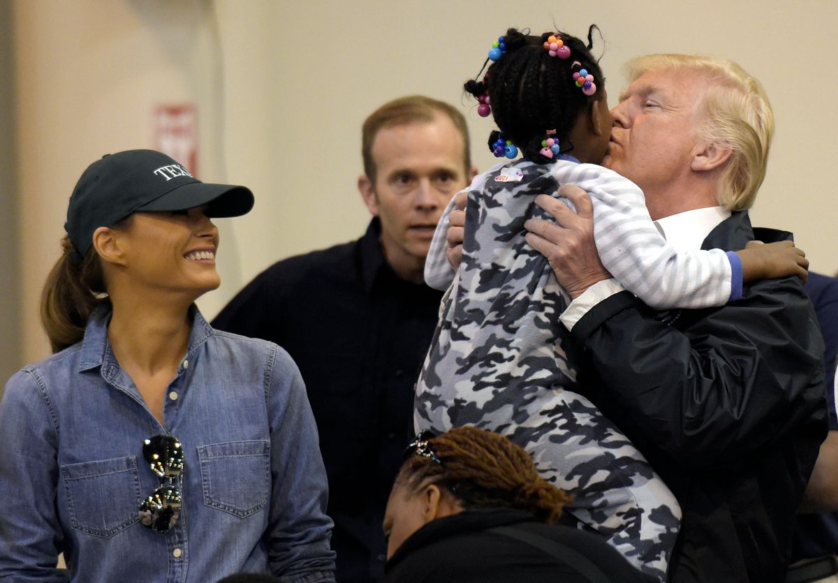 President Donald Trump and Melania Trump meet people impacted by Hurricane Harvey during a visit to the NRG Center in Houston, Saturday, Sept. 2, 2017.  He lifted this girl into his arms to give her a kiss.  It was his second trip to Texas in a week, and this time his first order of business was to meet with those affected by the record-setting rainfall and flooding. He's also set to survey some of the damage and head to Lake Charles, Louisiana, another hard-hit area. (AP Photo/Susan Walsh) (AP)