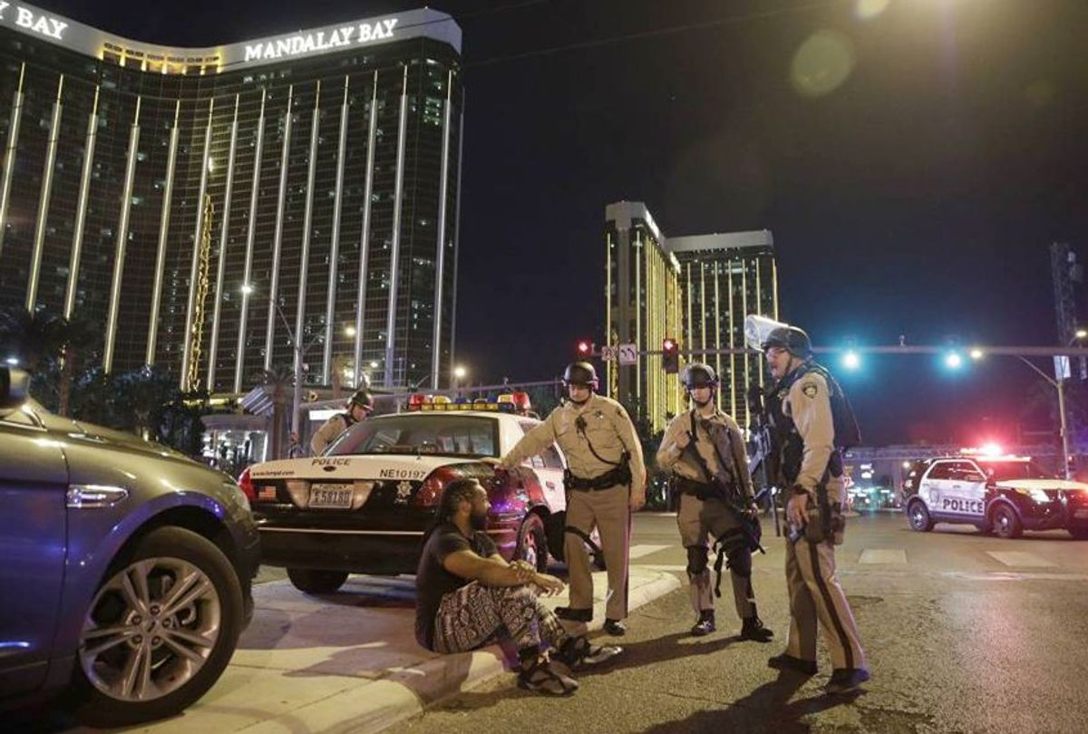 Police officers stand at the scene of a shooting near the Mandalay Bay resort and casino in Las Vegas, Oct. 1, 2017. (AP Photo/John Locher)