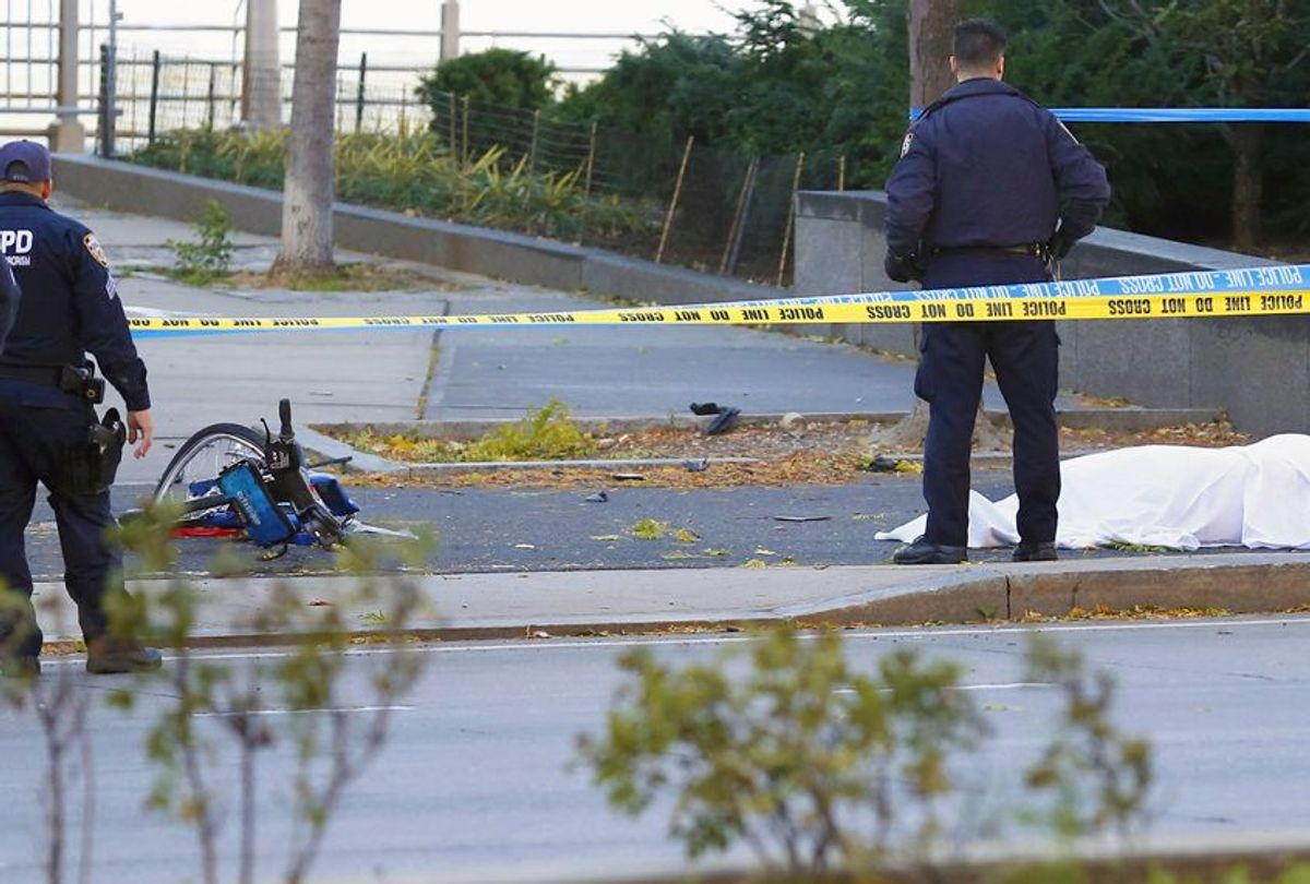 A New York Police Department officer stands next to a body under a white sheet near a mangled bike along a bike path, October 31, 2017 (AP/Bebeto Matthews)