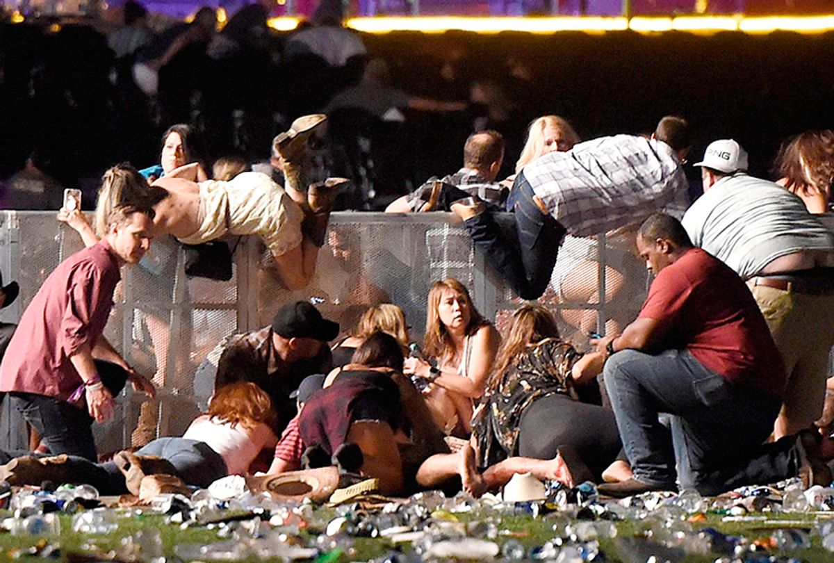 People scramble for shelter after gunfire at a country music festival on October 1, 2017. (Getty/David Becker)