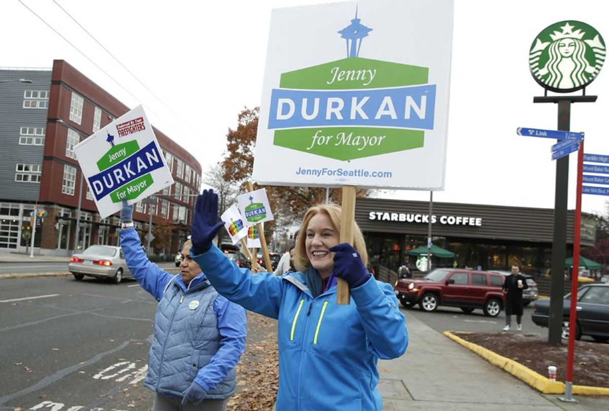Jenny Durkan, right, joins supporters waving signs on Election Day, Nov. 7, 2017, in Seattle. (AP/Ted S. Warren)