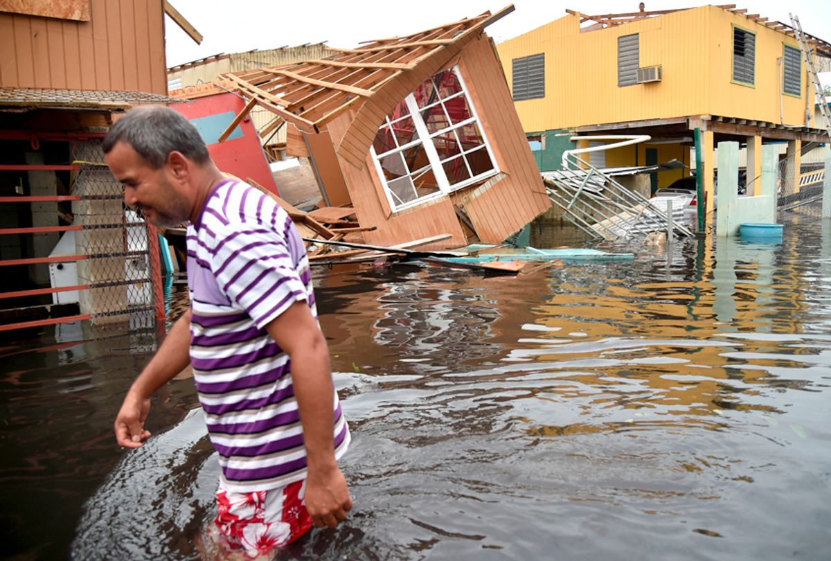 A man walks past a house laying in flood water in Catano town, in Juana Matos, Puerto Rico after Hurricane Maria (Getty/Hector Retamal)