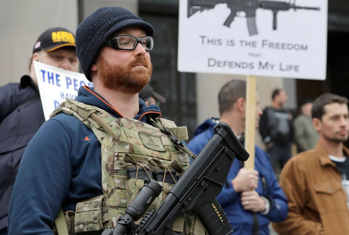 Ben Garrison  wears his Kel-Tec RDB gun, and several magazines of ammunition, during a gun rights rally at the Capitol in Olympia, Wash. (AP/Ted S. Warren)