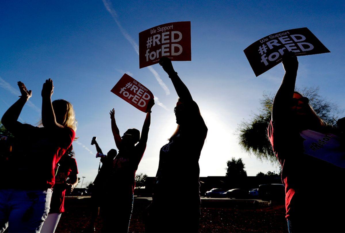 Teachers at Humphrey Elementary school participate in a state-wide walk-in prior to classes Wednesday, April 11, 2018, in Chandler, Ariz.  (AP/Matt York)