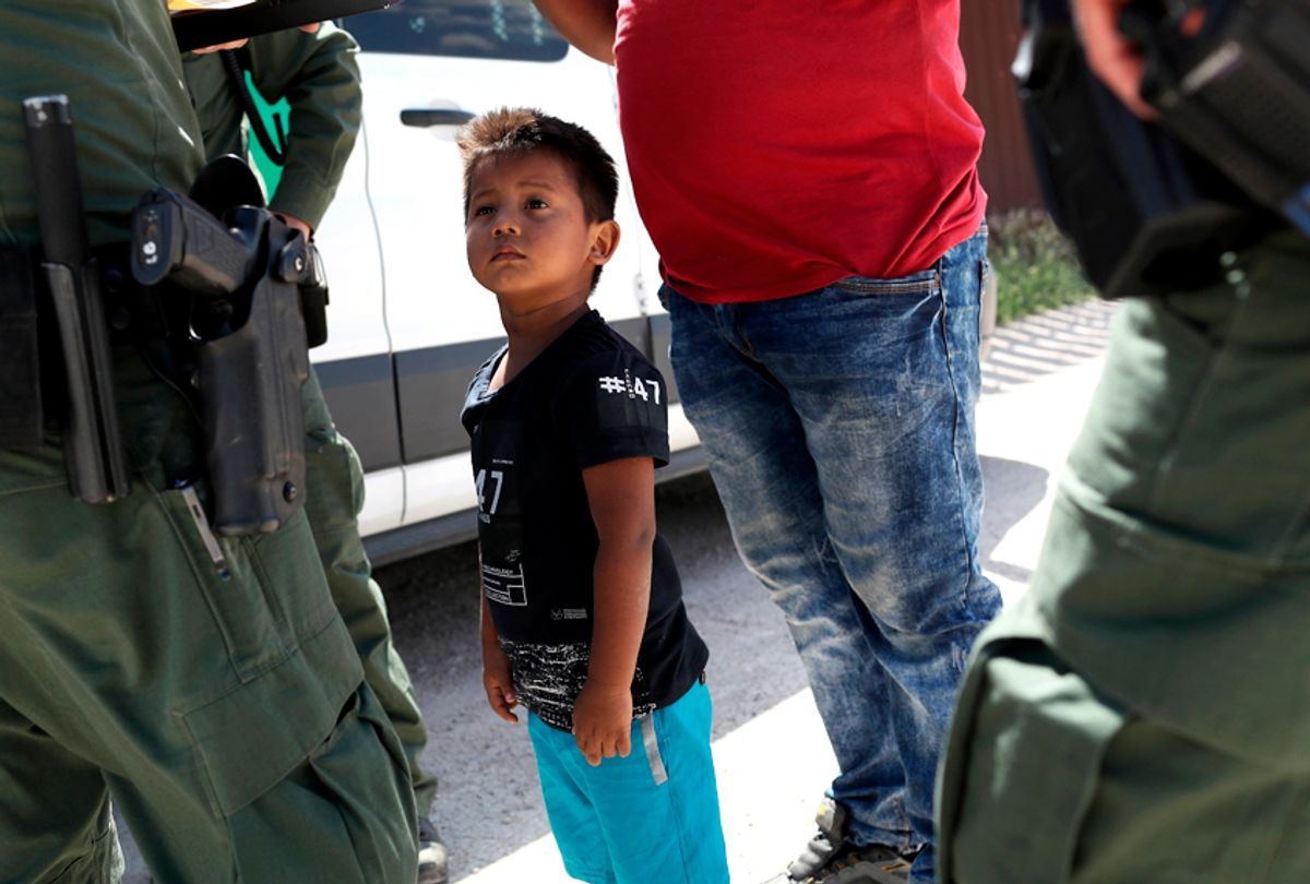 A boy and father from Honduras are taken into custody by U.S. Border Patrol agents near the U.S.-Mexico Border. (Getty/John Moore)