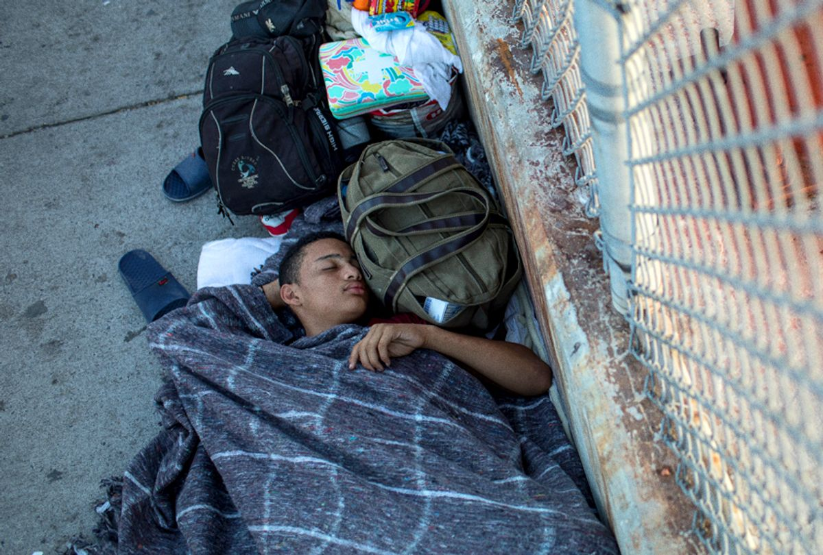 A 14-year-old boy from Honduras sleeps on the Mexican side of the Brownsville & Matamoros International Bridge, where he and his family have been waiting for days after being denied entry into the U.S., near Brownsville, Texas.  (Getty/Tamir Kalifa)