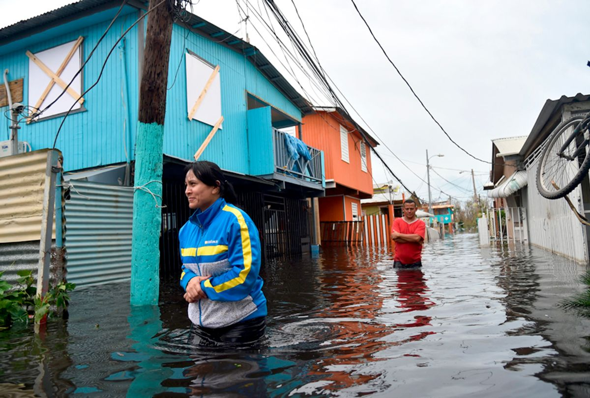 People walk across a flooded street in Juana Matos, Puerto Rico, on September 21, 2017 as the country faced dangerous flooding and an island-wide power outage following Hurricane Maria. (Getty/Hector Retamal)